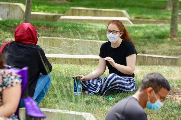 Socially distanced students in masks sit in the grass on campus