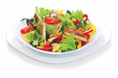 A salad with lettuce, chicken and yellow and red peppers on a white salad plate