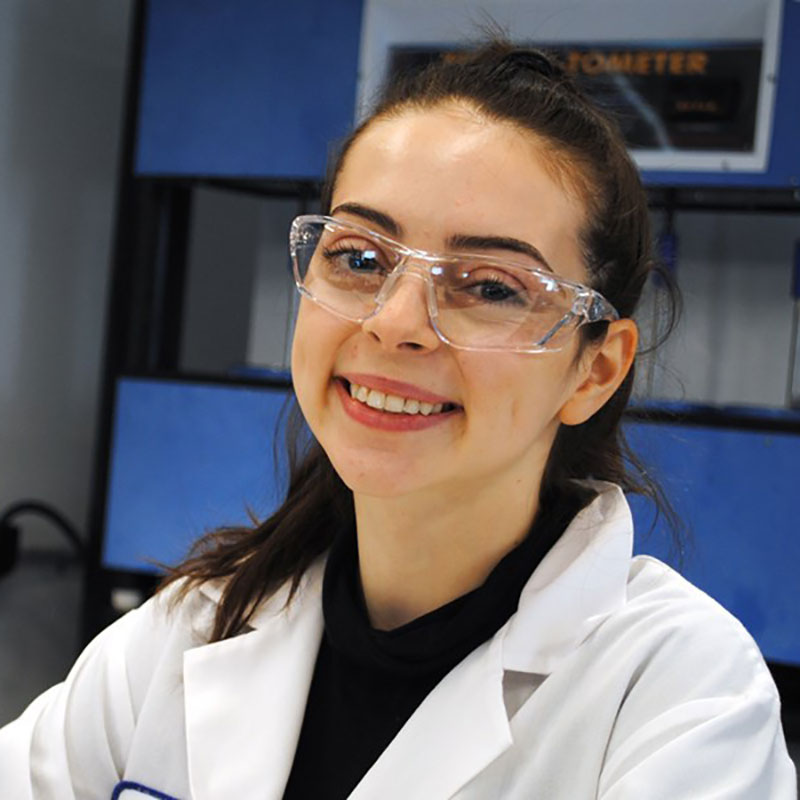 Smiling young woman in lab coat and goggles