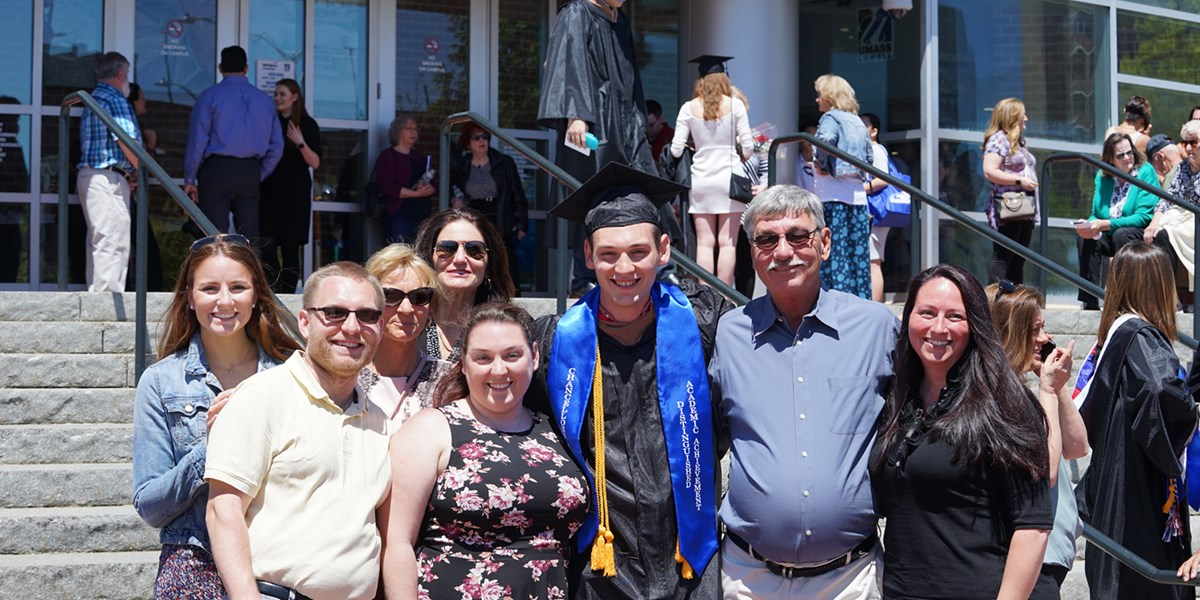 Sean Flaherty in cap and gown poses with his family outside of the Tsongas Center after UMass Lowell's 2019 Commencement