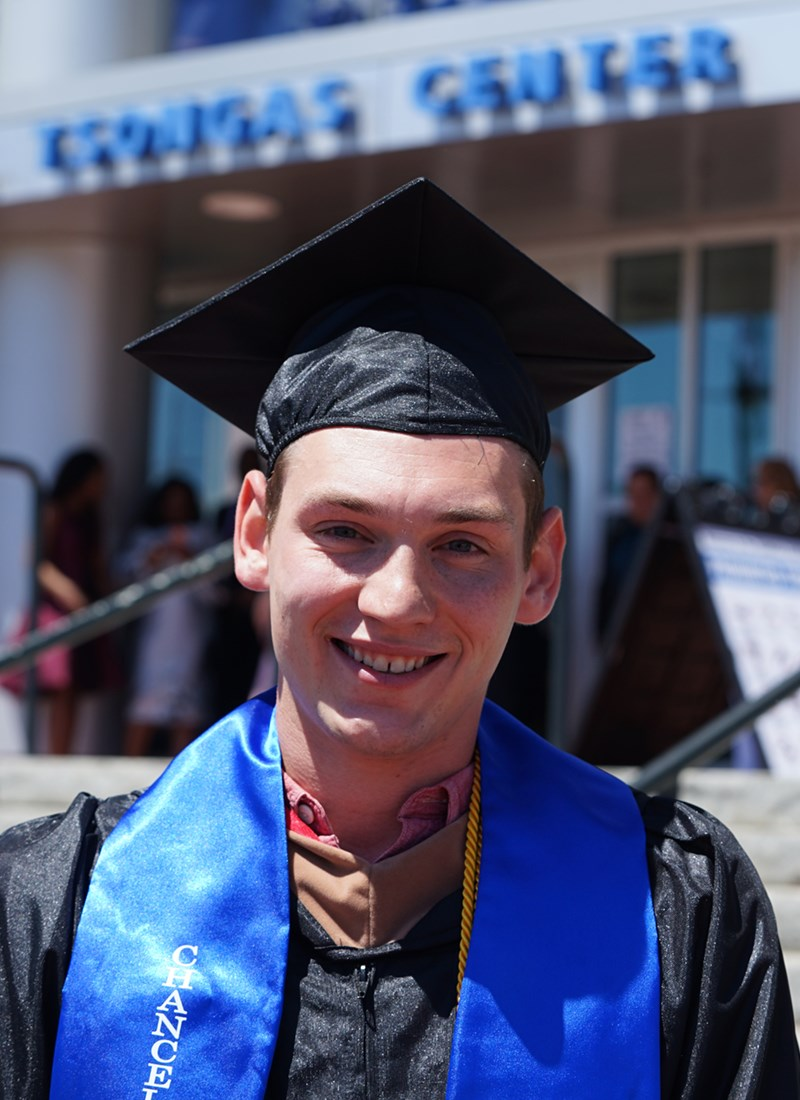 headshot of Sean Flaherty in cap and gown outside of the Tsongas Center after UMass Lowell's 2019 Commencement