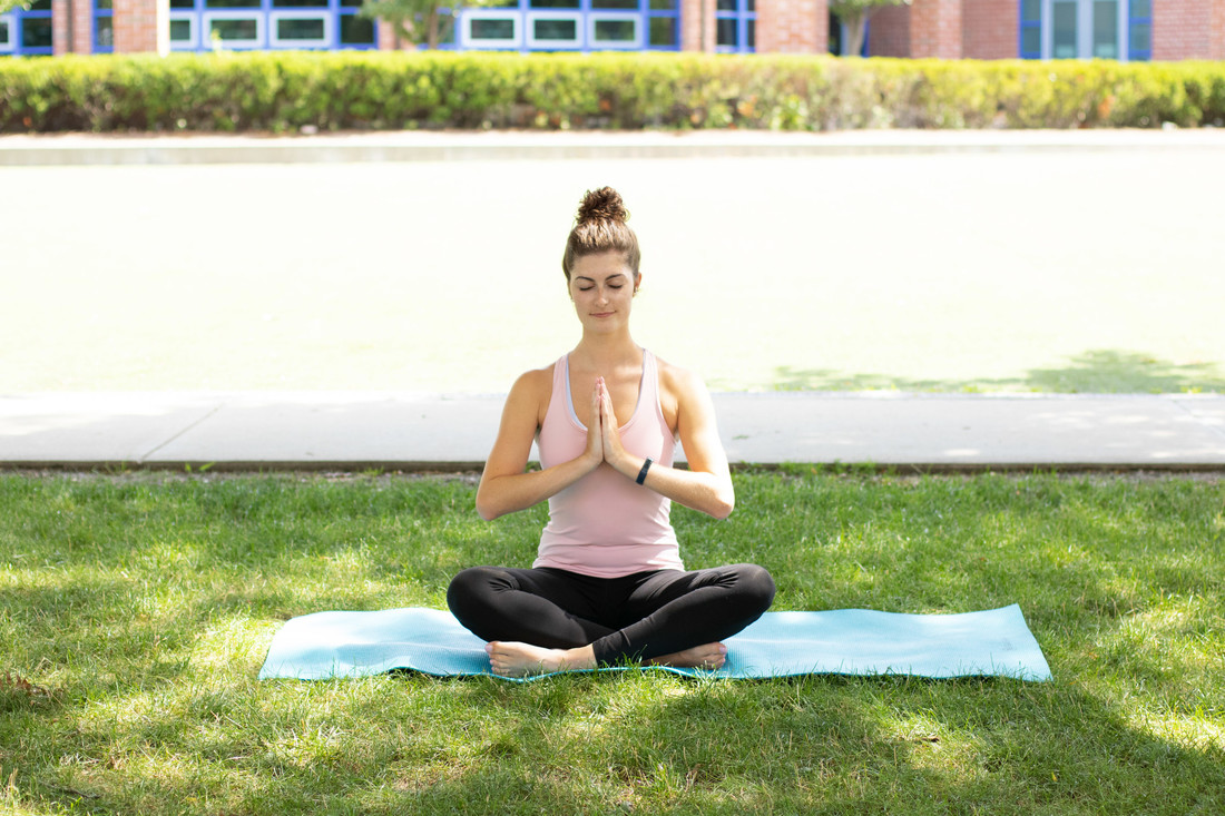 A yoga instructor demonstrates a seated meditation pose outside Campus Rec