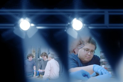 Photo collage showcasing photos of two seniors getting hands-on experience before they graduate in 2018 against a backdrop of spotlights with #UML2018