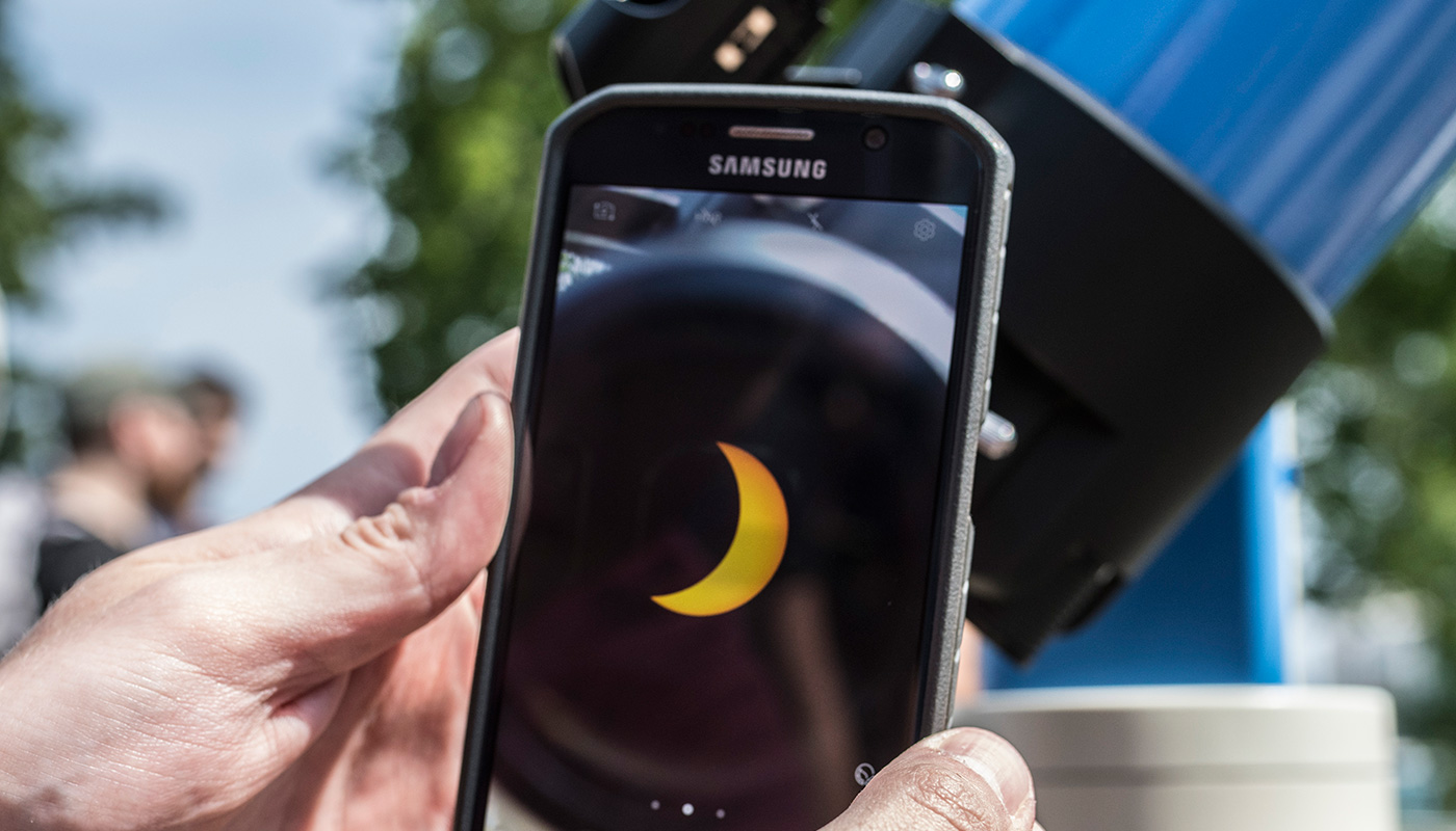 Person looking at solar eclipse on phone