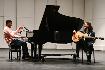 Dominik Hyppolite on piano and Alec Anand on guitar share a lighter moment during rehearsal