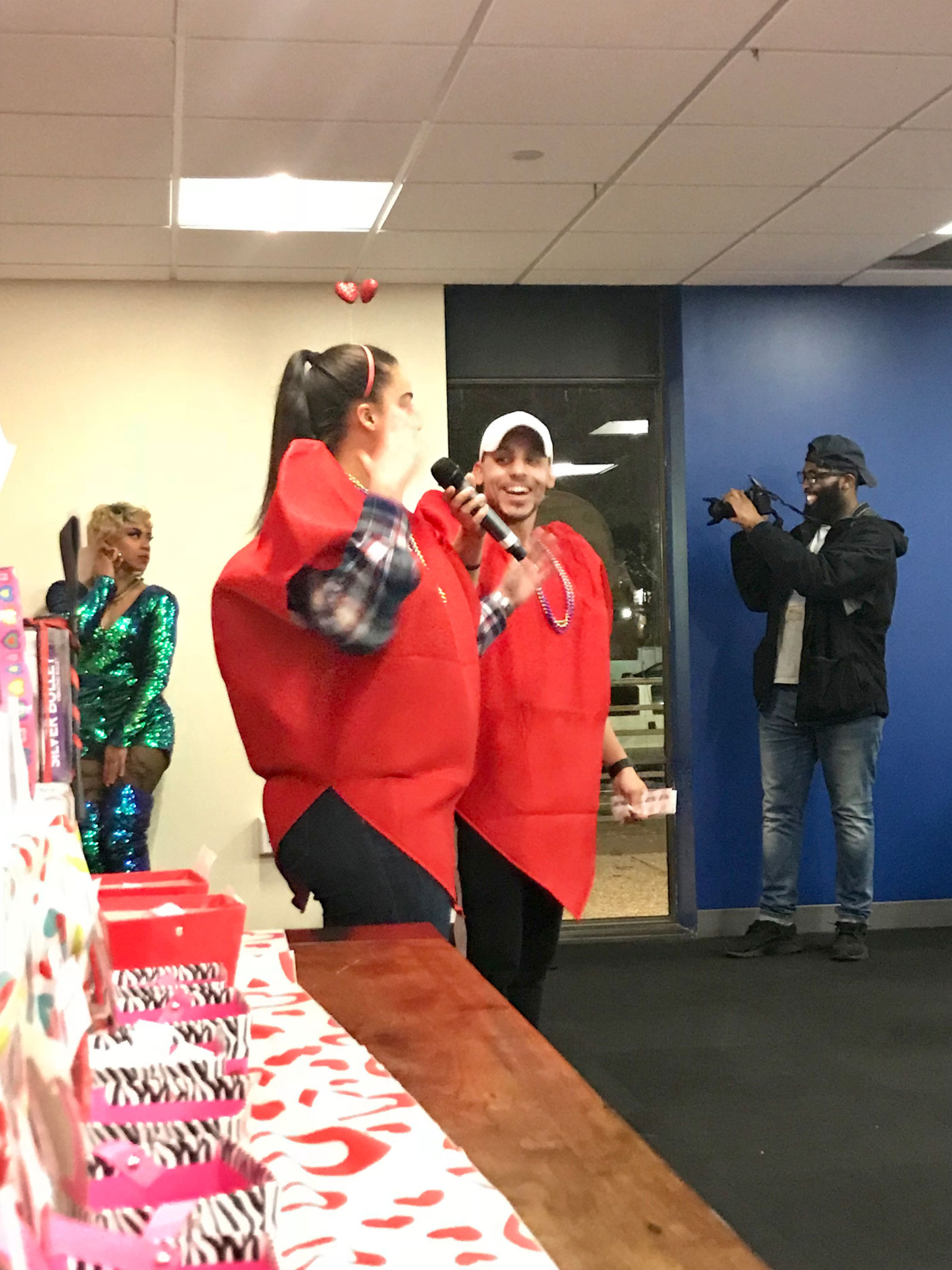 Two students wearing heart costumes and speaking to the audience at the Seaxpalooza Valentine's Day sexual health party.