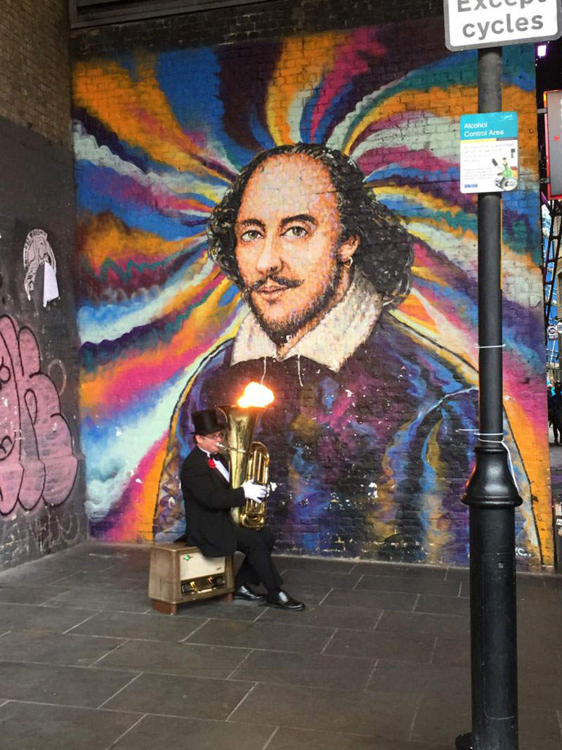 Musician playing in front of a Shakespeare mural at the Globe Theatre in London. Picture taking during a UMass Lowell study abroad trip.
