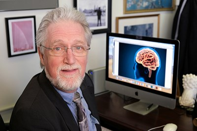 Prof. Thomas Shea in front of computer with brain on screen