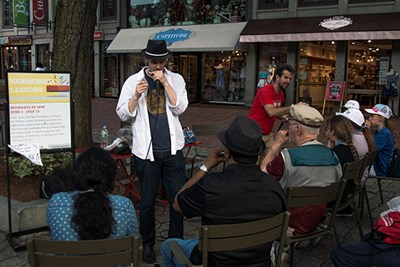 John Shirley teaches a harmonica class at Faneuil Hall