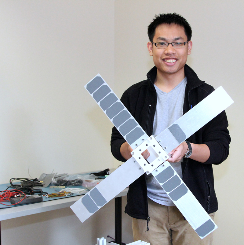 Simthyrearch Dy poses holding a scale model of SPACE HAUC, UMass Lowell's first student-built satellite