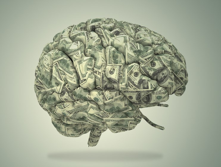 A photo of a human brain sculpted out of $100 bills on a green background.