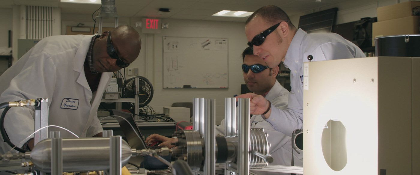 Three solar energy researchers working in a lab.