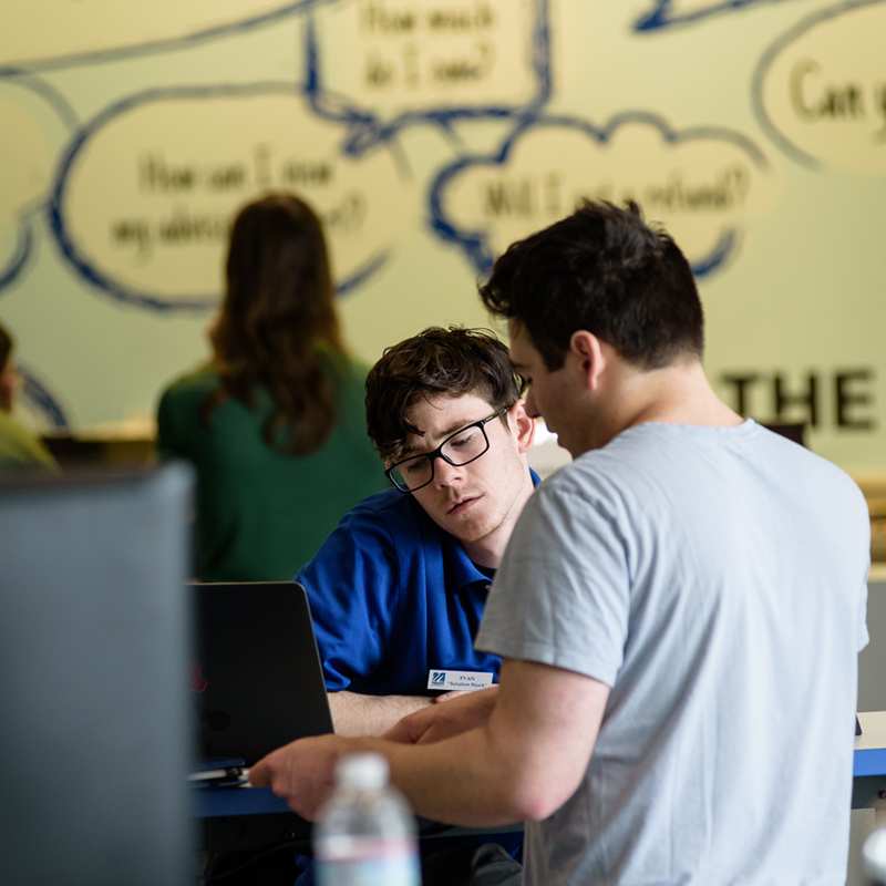 A student gets helped by a staff member at UML's Solution Center