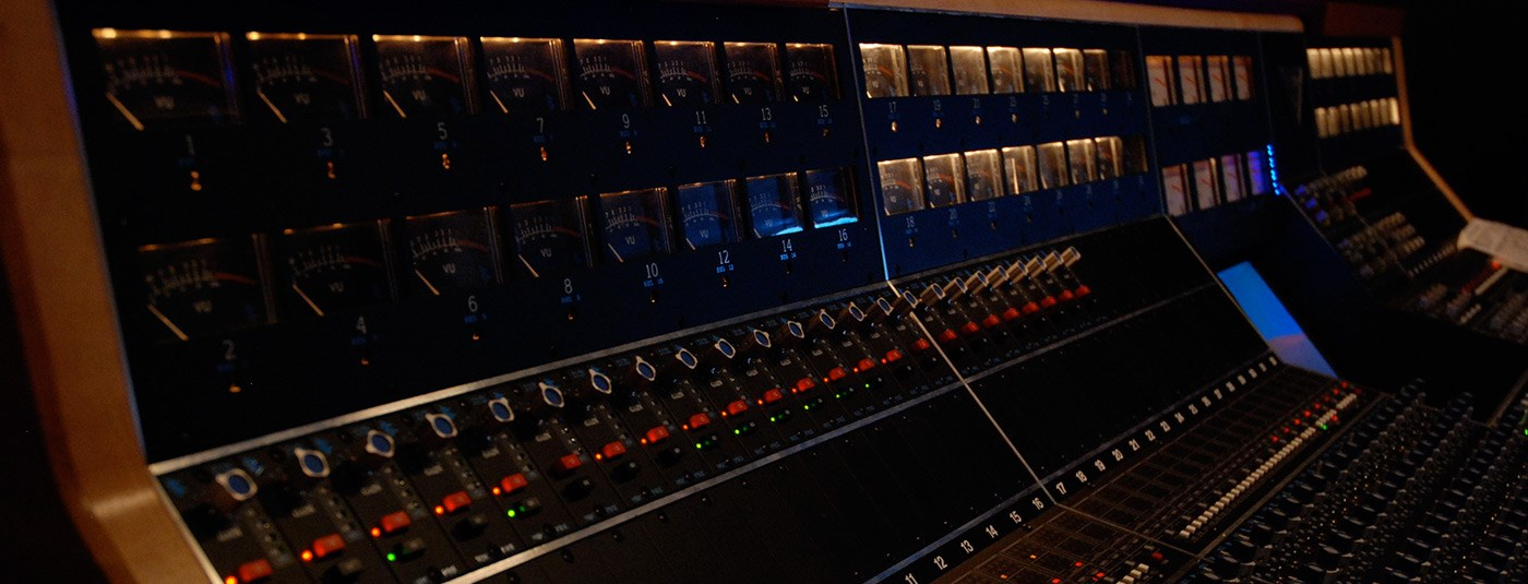 A side view of a soundboard in a studio of the Sound Recording Technology program.