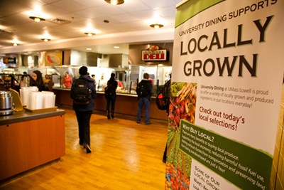 """Locally Grown"" sign featuring a list of some of Southwick Dining's locally grown produce, students getting lunch in the background"