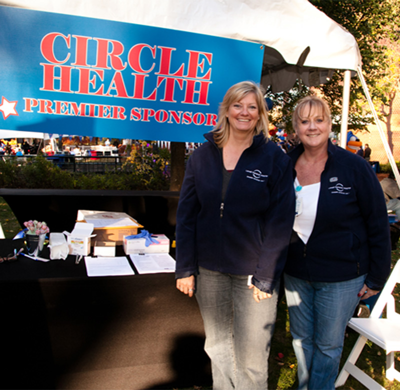 Two women from Circle Health in front of their tent