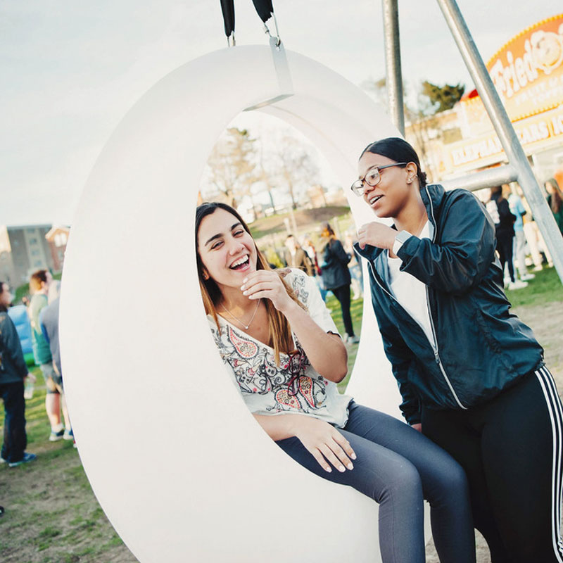 two female students on swing seat at UML spring carnival