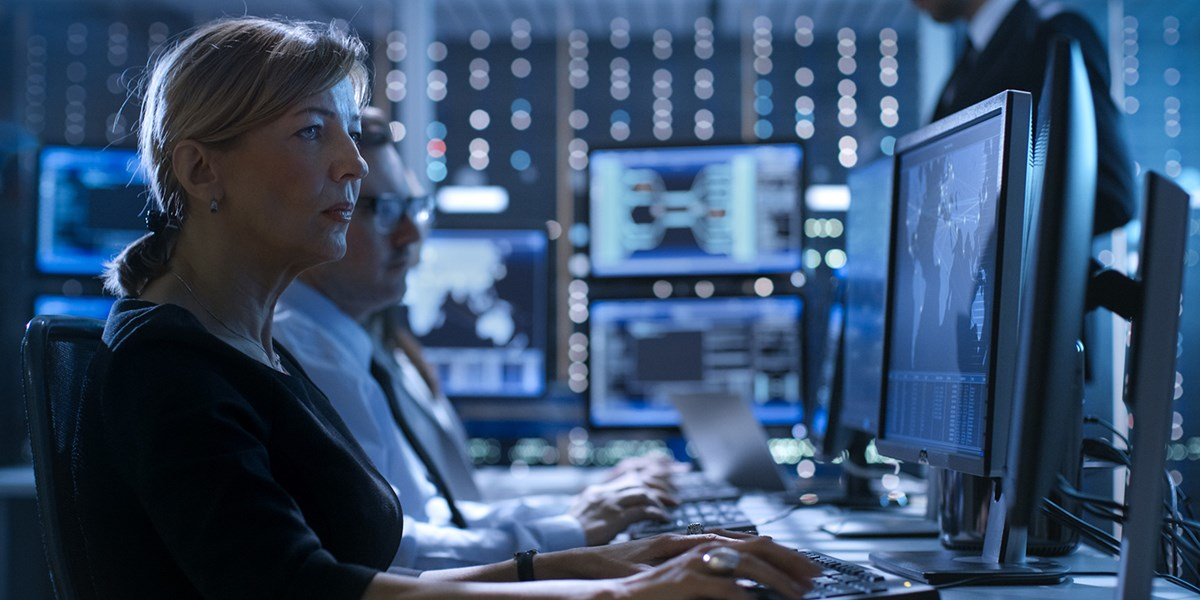 Stock image: Female Government Employee Works in a Monitoring Room. In The Background Supervisor Holds Briefing. Possibly Government Agency Conducts Investigation.