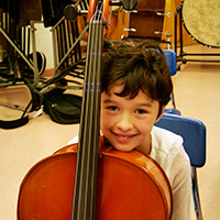 A child from the String Project poses backstage with his cello before the concert.