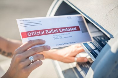 a person drops a mail-in ballot into a mailbox