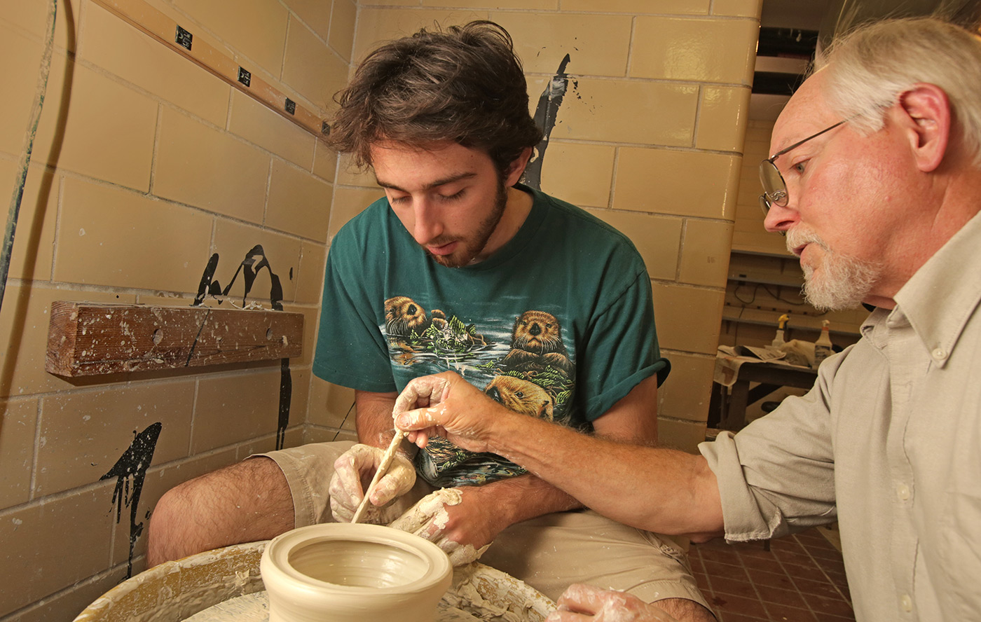 A student and professor work on a pottery wheel.