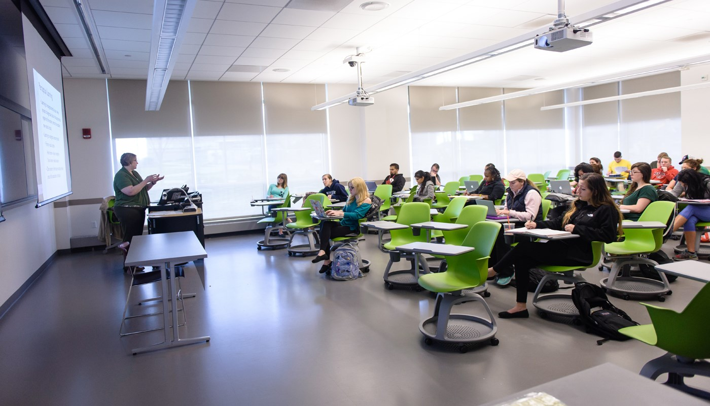 Students in class with professor in UMass Lowell's Health & Social Sciences building