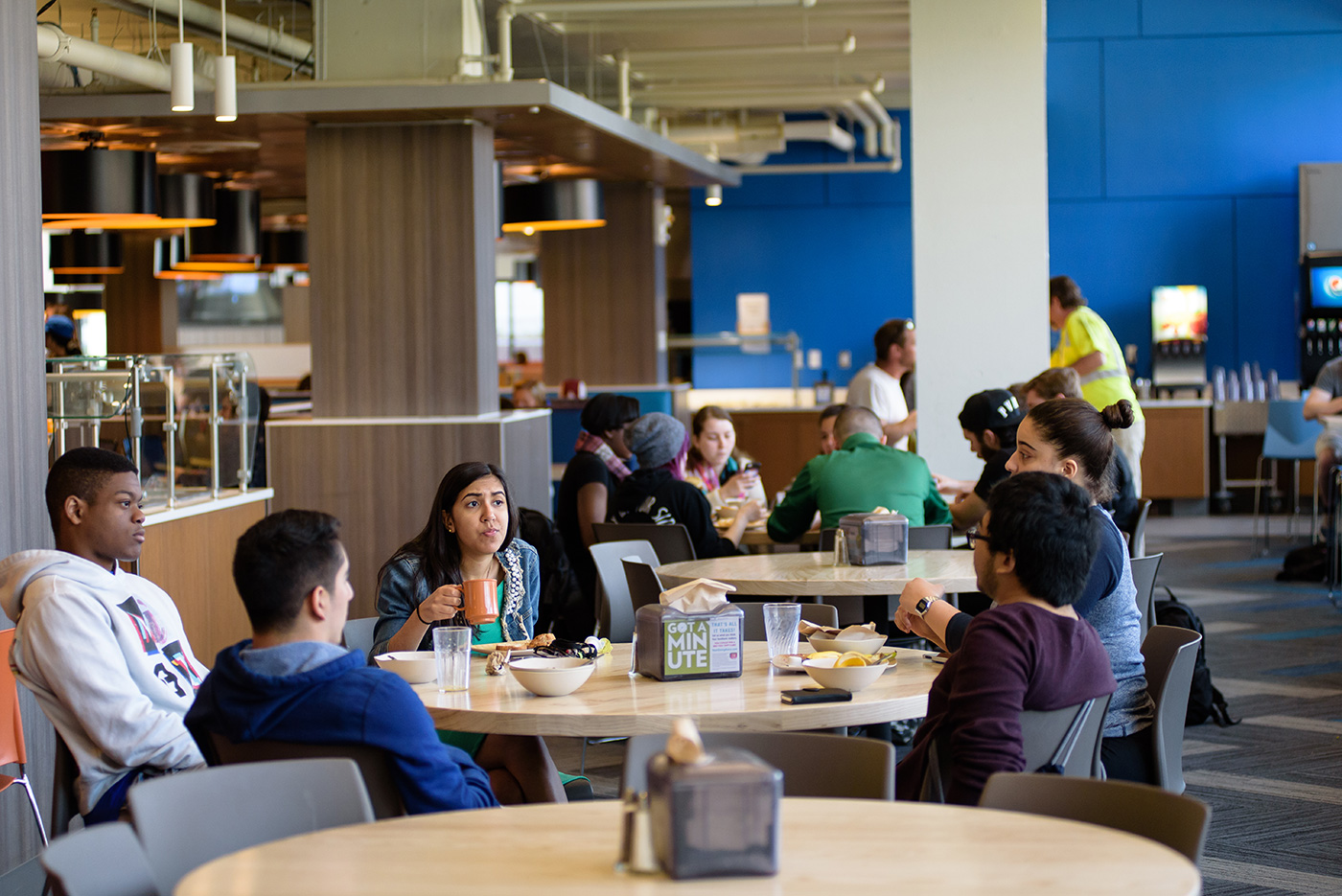 Students eating and talking around a table at the South Campus Dining Commons in the McGauvran Center.