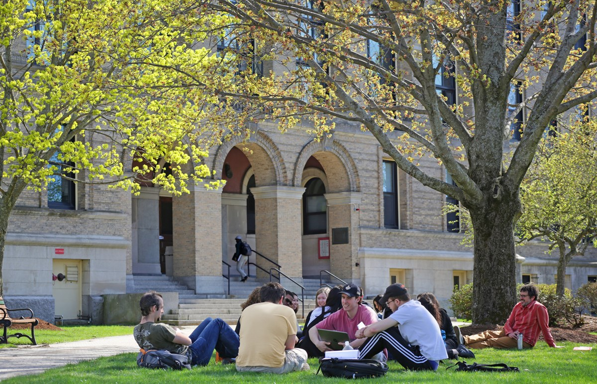 students lounging on grass in front of hall