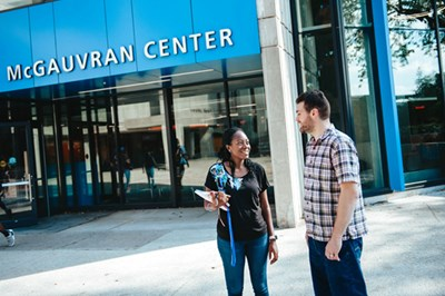 Two students talk outside of McGauvran Center at UMass Lowell