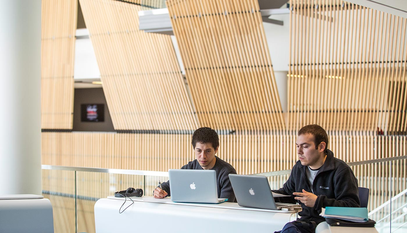 Two men with laptops studying in University Crossing