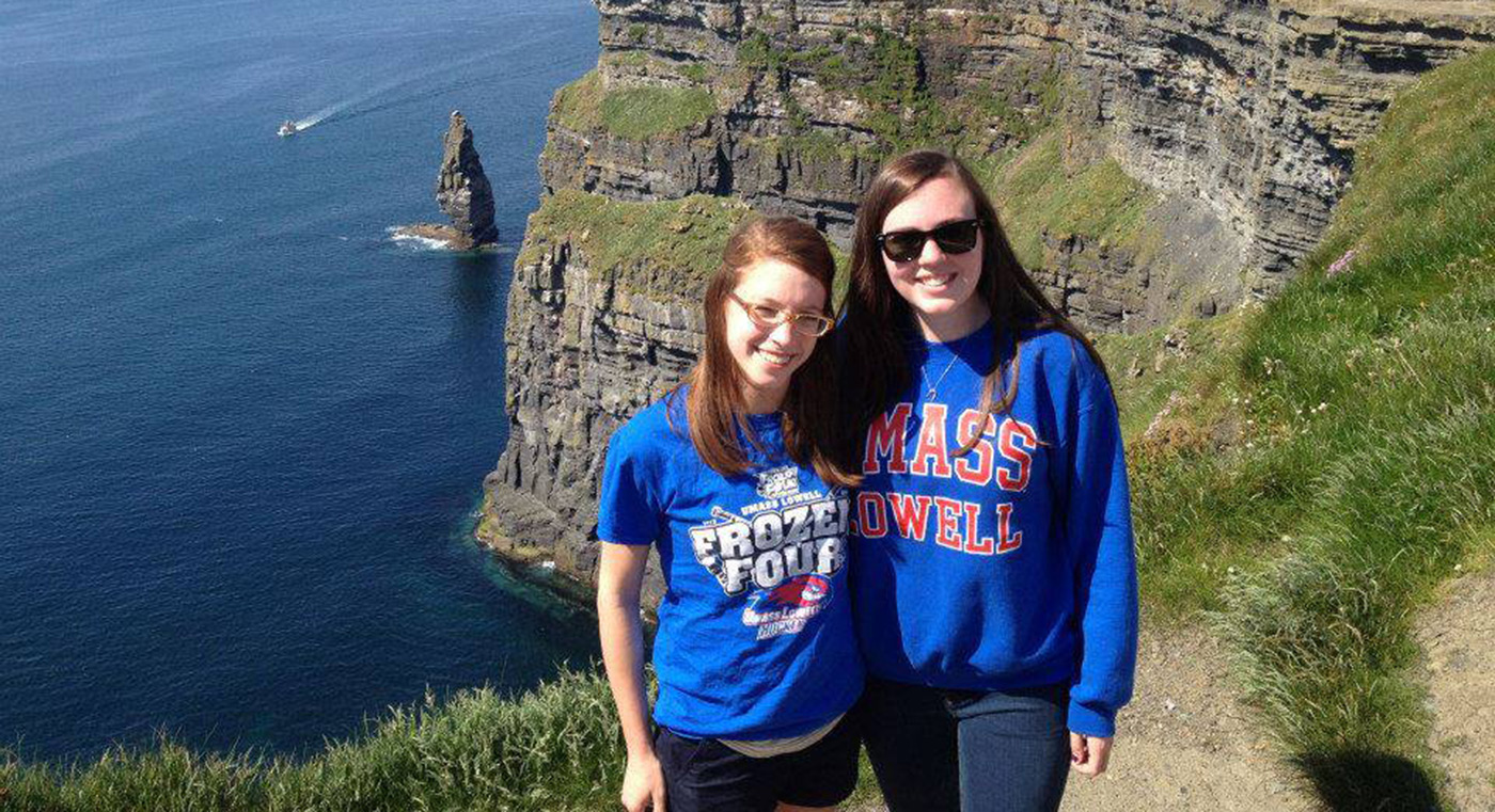 Two female UMass Lowell students pose for a photo on the Irish coastline.