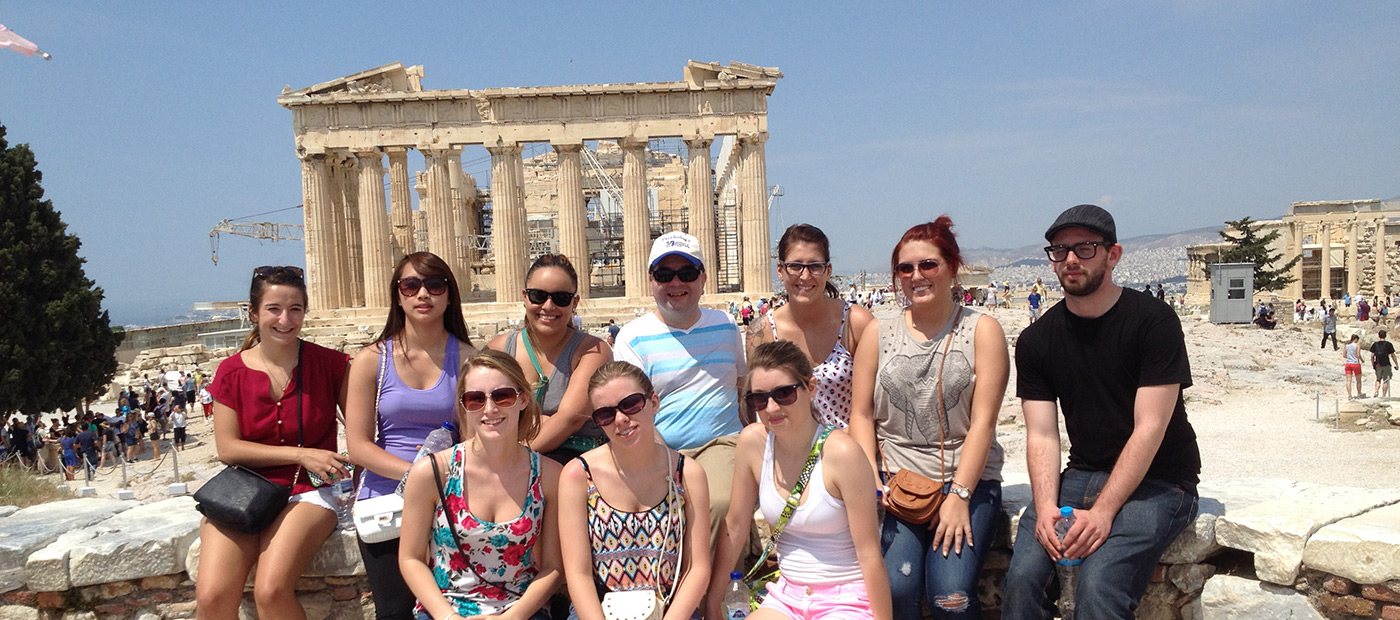 A group UMass Lowell Study Abroad students pose for a photo in front of ruins in Greece.