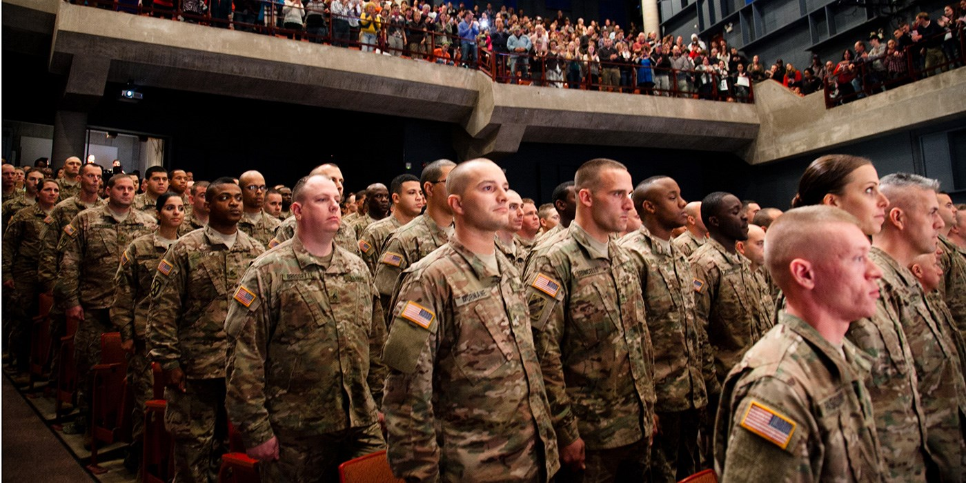 Fatigue-clad troops standing in auditorium