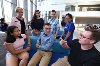 UMass Lowell Chancellor Jacqueline Moloney with students Andrea Miles, William Zouzas, Monica Kong, Thomas Brennan, David Morton, and Linh Phan at University Crossing