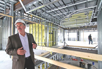 """Downtown doesn't have to stop at City Hall,"" said Jeanne D'Arc Credit Union President and CEO Mark Cochran, shown Friday touring the credit union's three-story building rising at 585-597 Merrimack St."