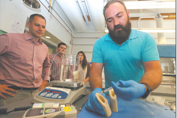 LaunchPad CEO and founder Brian Hess of Chelmsford, biomechanical engineer and co-founder Andrey Marchenko of Acton, and product development engineer Christy Cavaleri of Billerica, watch R& D program manager Mike Brown of Andover apply the glue to a piece of bone.