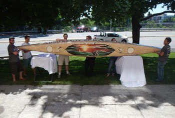 UMass Lowell engineering students lift their 132-pound concrete canoe on its side to display a painting.