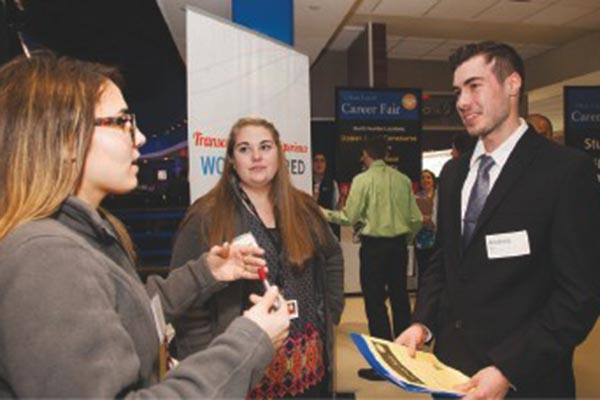 Andrew Gys, right, of Dracut, a business administration major at UMass Lowell, speaks with recruiters Nicole Neves, left, and Maggie Carter of Kronos about opportunities at the labor-management software company. PHOTO / Meghan Moore for UMass Lowell