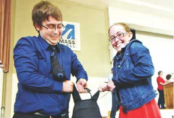 UML biology majors, Jared Nease, a junior, of Medford, and Kacey Hill, a senior, of Groveland, lift a backpack with 100 pounds of weights to help demonstrate the average an American's carbon emissions per day during a climate-change event at Cumnock Hall Thursday. Sun/Bob Whitaker