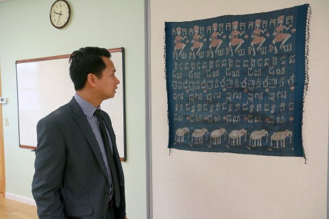 Sovanna Pouv, executive director of the Cambodian Mutual Assistance Association in Lowell, talks about the Cambodian flag that hangs in the classroom at the agency's Lowell headquarters on Wednesday. Many Cambodian pieces of art adorn the walls of the center.