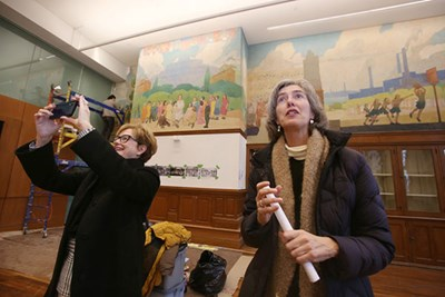 Chancellor Jacqueline Moloney and Art professor Marie Frank look at the relief sculptures in the large hall of Coburn Hall