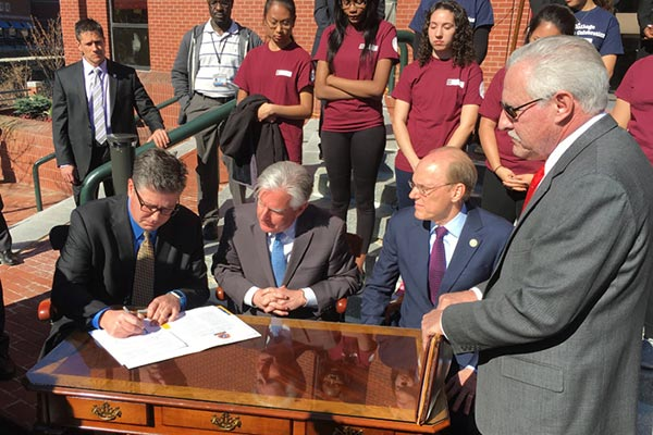 From left, Worcester State University President Barry Maloney signs the Commonwealth Commitment on the steps of Middlesex Community College in downtown Lowell Thursday morning as UMass President Marty Meehan, MCC President James Mabry and Higher Education Commissioner Carlos Santiago look on.
