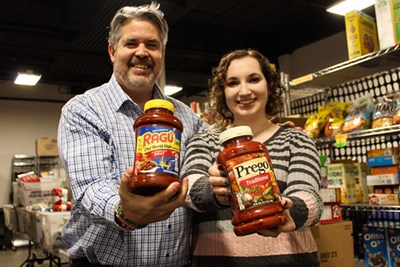 Kevin Willette poses with volunteer Meaghan O'Brien and jars of spaghetti sauce