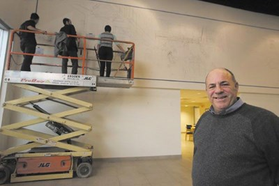 Salesman James Dabilis of Lowell, right, enjoys watching the mural take shape in the Drum Hill Ford showroom thanks to the talent and skills of Carlos Pujols, Josh Rondeau and Courtney LeMay.