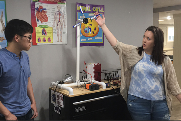 "UMass Lowell senior Katie Elwell, 22, of Tewksbury, demonstrates the wind turbine component of the renewable energy ""traveling classroom"" she and senior Benjamin Tran, 21, of Quincy, left, created for Girls Inc. of Greater Lowell for their mechanical engineering capstone project."