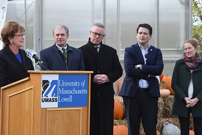 UMass Lowell Chancellor Jacquie Moloney, left, speaks at the UMass Lowell greenhouse while other look on.