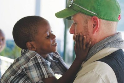 Trinity EMS EMT Dave Roberts, of Tyngsboro, is warmly greeted by a Haitian child at an orphanage during a recent mission to that island nation.
