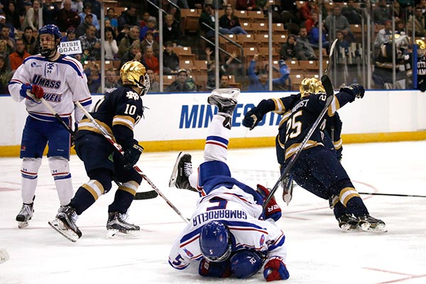 UMass Lowell s Joe Gambardella (5) and John Edwardh fall to the ice as Notre Dame players celebrate their game-winning goal during the first overtime period in Manchester, N.H.
