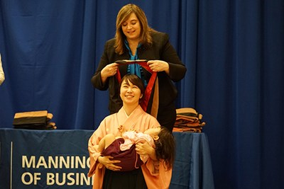 Tomoe Yashida holds her daughter as Dean Sandra Richtermeyer placed a ceremonial hood over her head