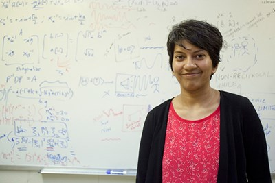 UMass Lowell physics professor Archana Kamal stands in her office in front of a whiteboard covered with formulas and notes.